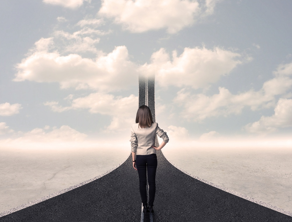Business woman looking at road that goes up in the sky concept.jpeg