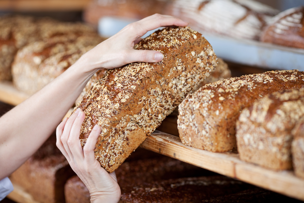 Cropped image of female bakery workers hands removing whole grain bread loaf from shelves
