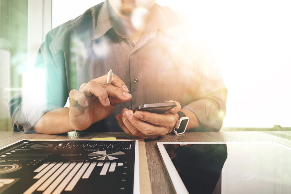 businessman working with digital tablet computer and smart phone with digital business strategy layer effect on wooden desk as concept.jpeg